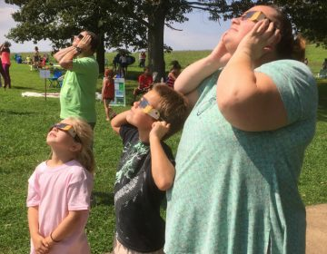 Families wore eclipse glasses to look up at the natural phenomenon.(Zoë Read/WHYY)