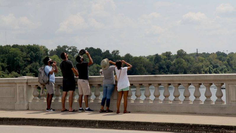 People gather on the Gervais Bridge in Columbia, South Carolina, to view the total solar eclipse. (Kimberly Paynter/WHYY)