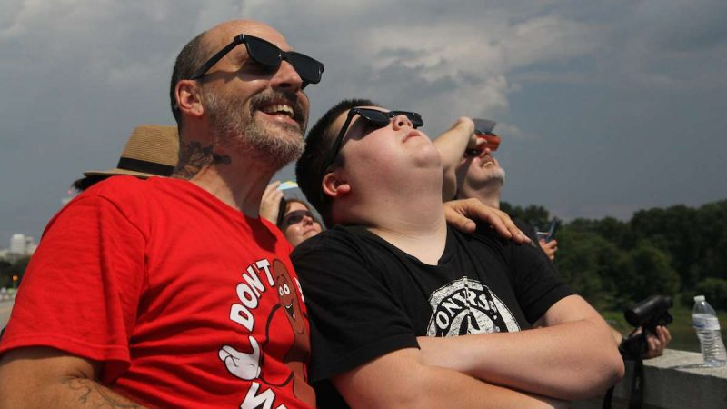 Louis and Parker Reed view the 2017 solar eclipse in Columbia, South Carolina. (Kimberly Paynter/WHYY)