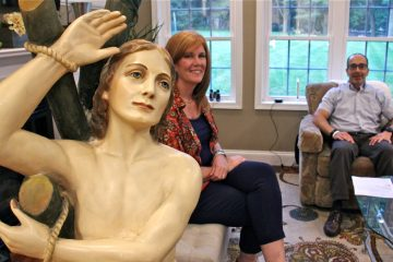 Ed and Kathleen Nader sit in their living room with a statue of St. Pantaleone that has been in Ed's family for four generations. (Emma Lee/WHYY)