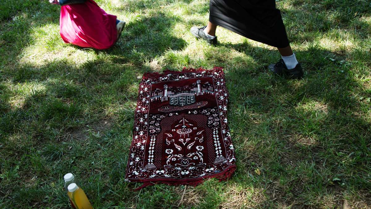 A prayer rug lies in the grass in Clara Muhammad Square
