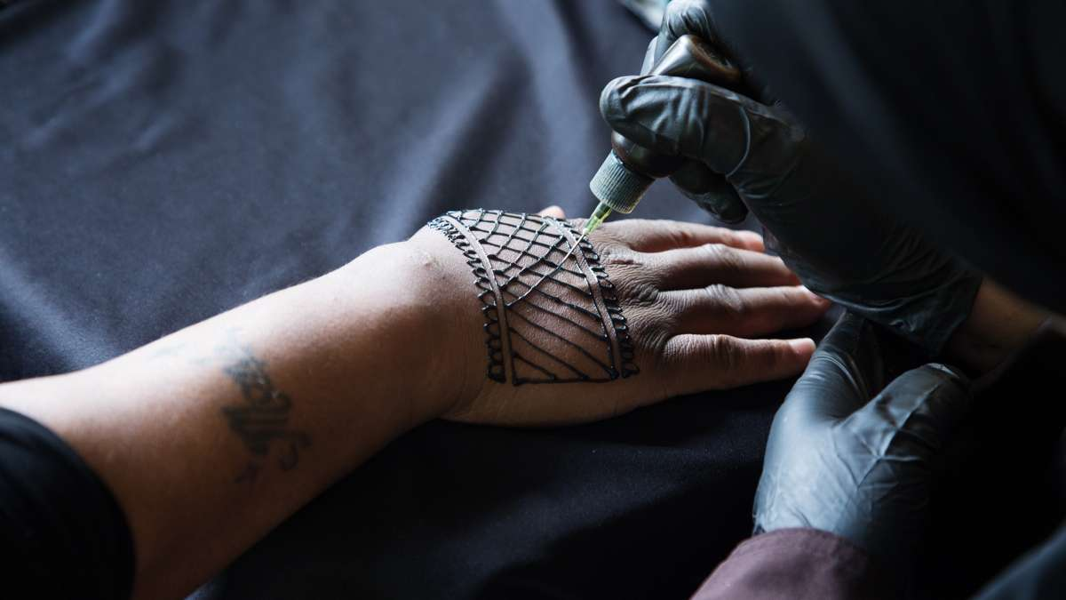 A woman paints henna on to the hand of a client at FDR Park
