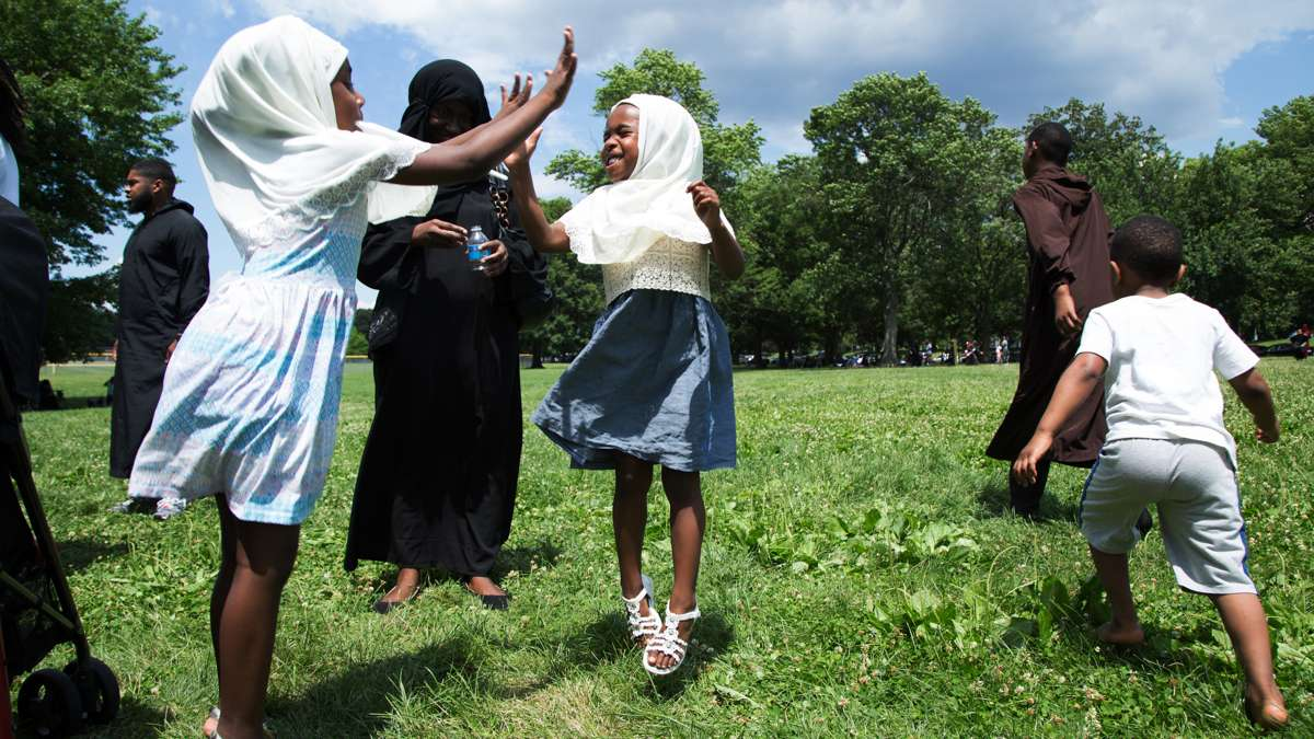 Two sisters jump and play while at Eid al-Fitr festivities in FDR Park