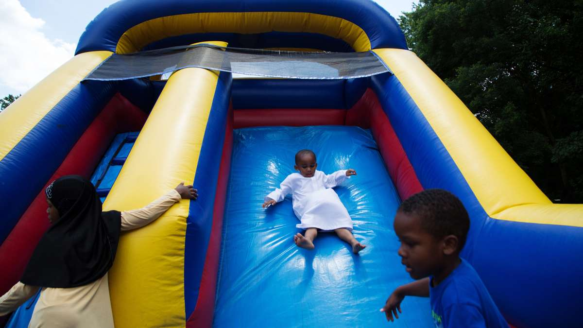 A young boy slides down an inflatable slide