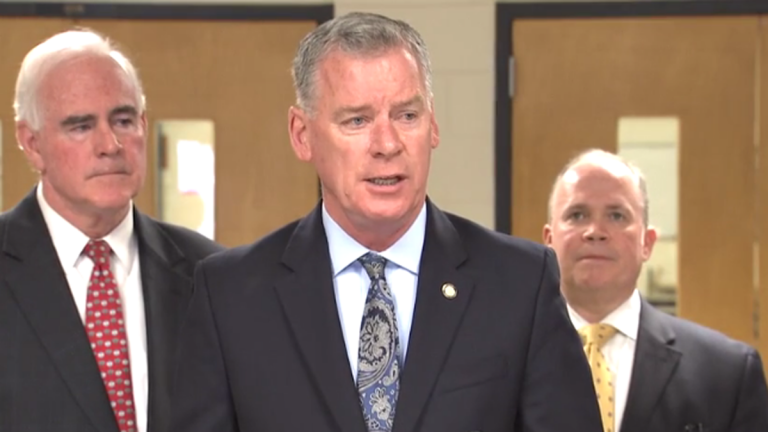 State Senator Tom McGarrigle speaks about his plans to introduce a bill diverting federal housing subsidies from tax delinquent landlords at a news conference in the William Penn School District. (Laura Benshoff/WHYY)