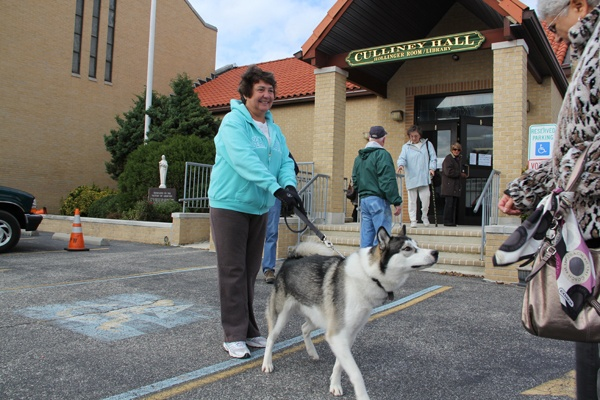 <p>Kathleen Wheatcraft waits with her dog outside of St. Francis Cabrini Church, a busy polling place in Ocean City. (Emma Lee/for NewsWorks)</p>
