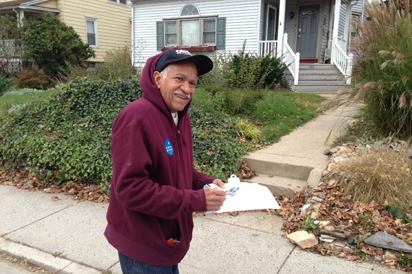 <p>Volunteer Samuel Brackeen was knocking on the doors in Glenside encouraging anyone at home to vote.  For those who were not in, he was leaving a reminder sticker.  (Jeanette Woods/WHYY)</p>