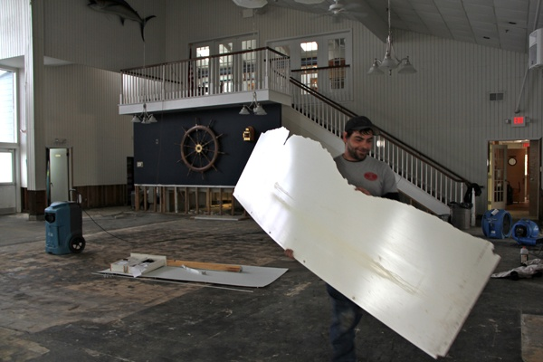 <p>Ed Colavita helps to clean out the Ocean City Yacht Club after it was innundated by Hurricane Sandy. Those who usually vote at the club were sent to a nearby church to cast their ballots. (Emma Lee/for NewsWorks)</p>
