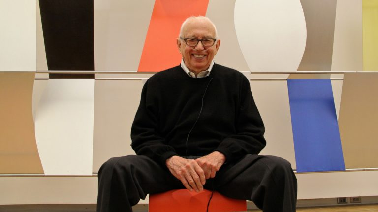 Ellsworth Kelly, who died Sunday at the age of 92, is shown sitting in front of his first monumental wall sculpture, 12 feet high and 67 feet wide. The work was exhibited at the Barnes in Philadelphia in 2013 for a celebration of the artist's 90th birthday.  (Emma Lee/for NewsWorks)
