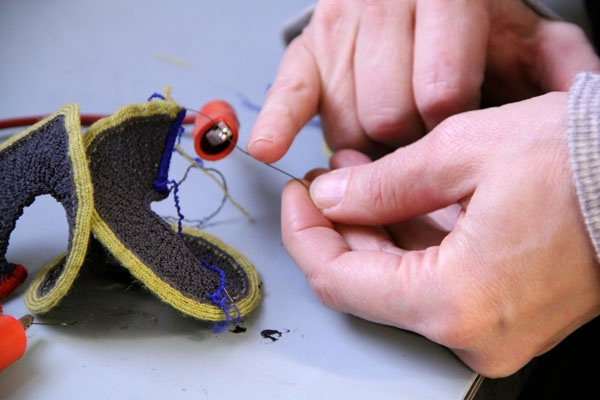 """<p><p>A wire made from nickel titanium, a shape memory alloy, controls the movement of the """"knitbot"""", a knitted robot being researched at Drexel's ExCITe Center. (Emma Lee/for NewsWorks)</p></p>"""