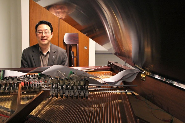 <p><p>Dr. Youngmoo Kim, director of Drexel's ExCITe Center, sits at his magnetic resonator piano. Electromagnets, rather than hammers, can cause the piano's strings to vibrate. (Emma Lee/for NewsWorks)</p></p>