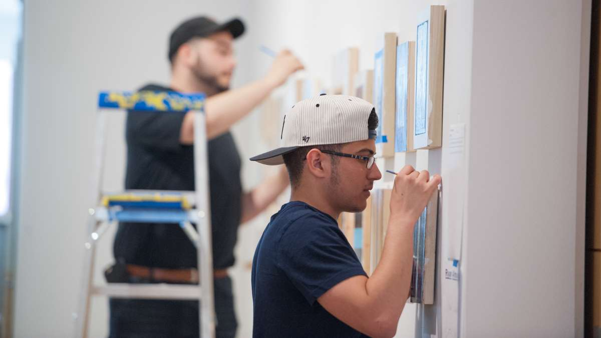 Diego Rodriguez Carrion (right) helps Ryan Almodovar install his work.