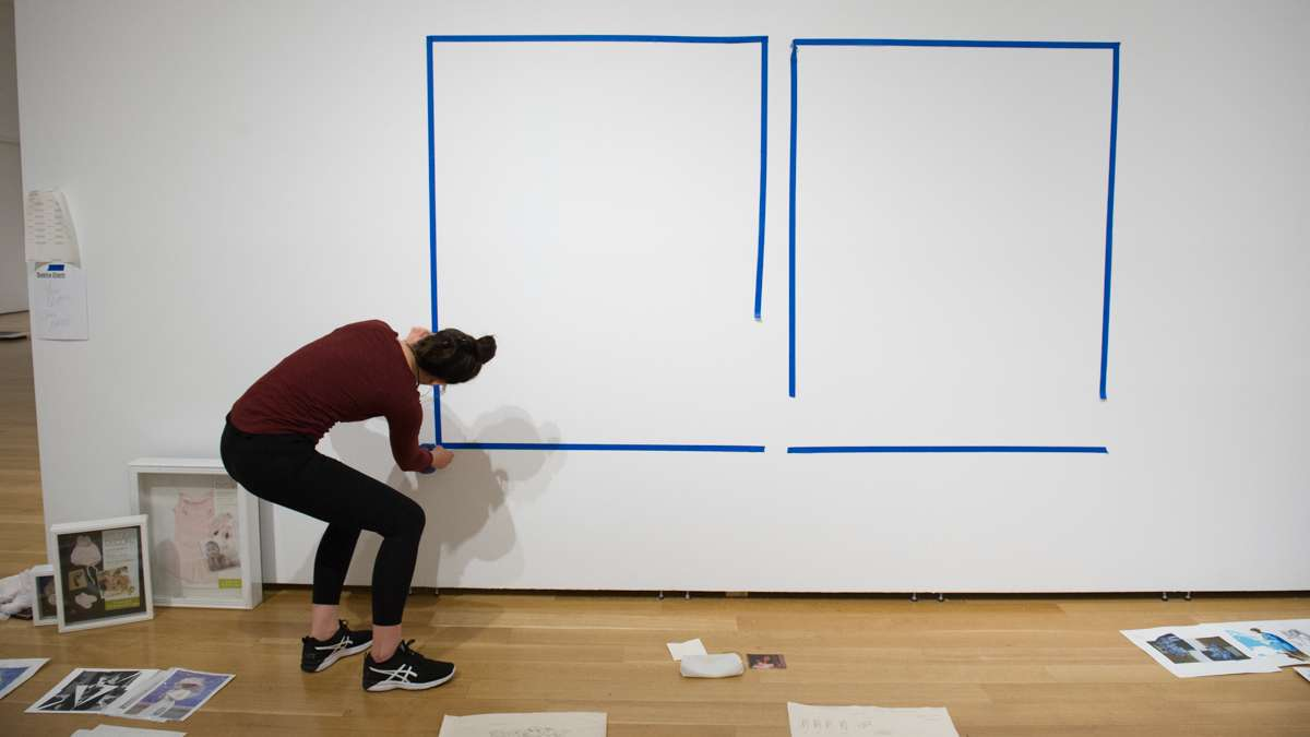 Sasha Diehl tapes the location of two of her large paintings on the gallery wall.