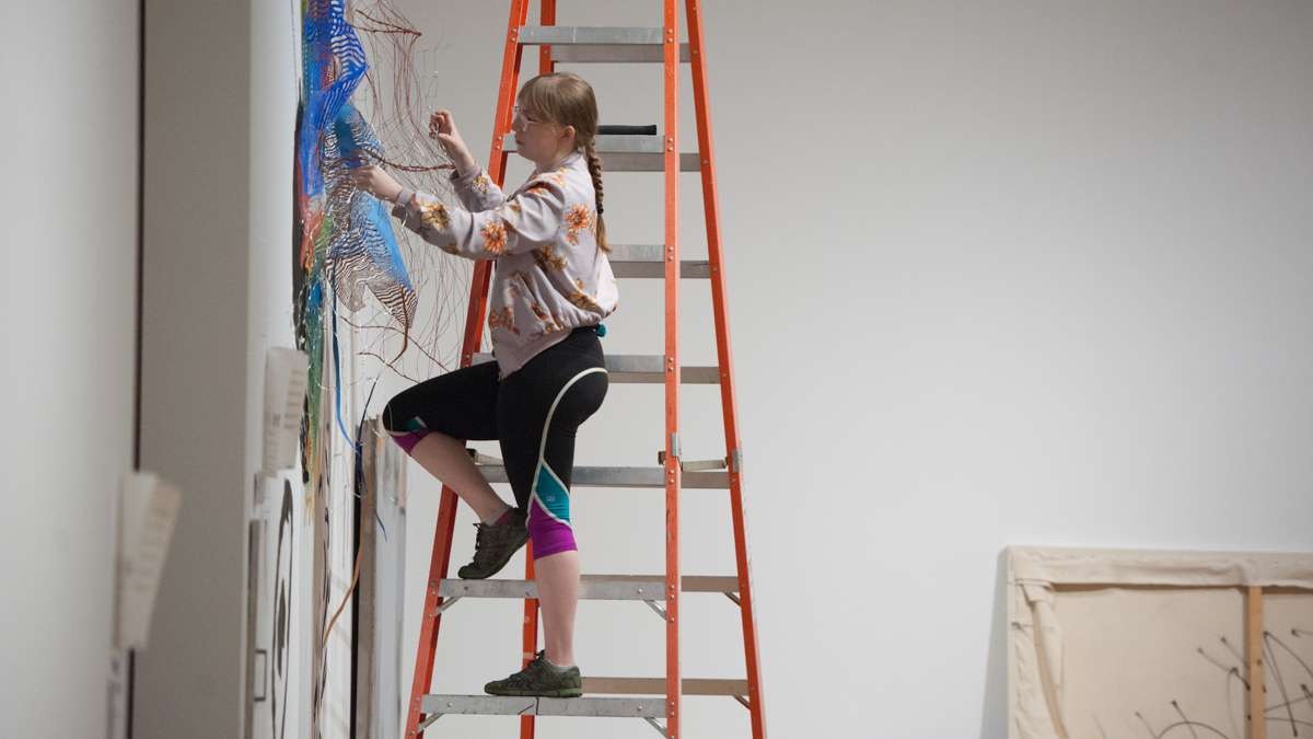 Justine Ditto works on a wall installation.