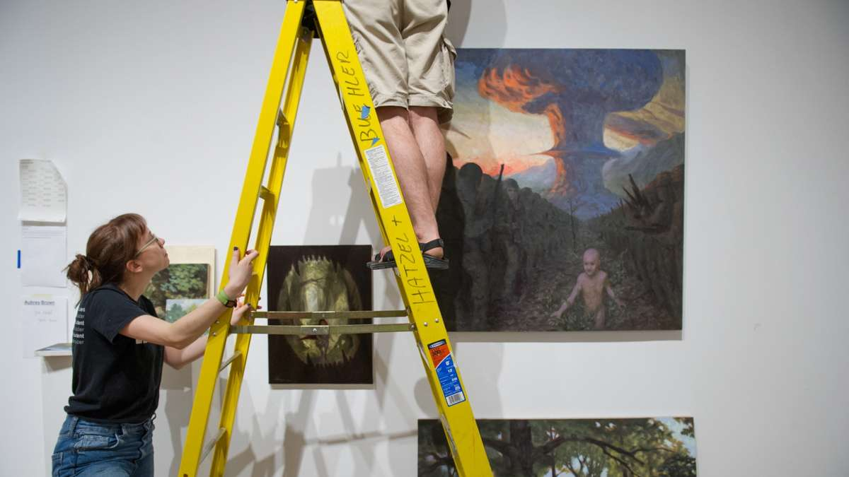 PAFA Alumni Zoe Zurad holds the ladder for Aubrey Brown as he hangs his paintings.