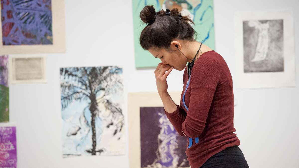 With her paintings laid out on the floor, Sasha Diehl contemplates hanging her work on the gallery wall.