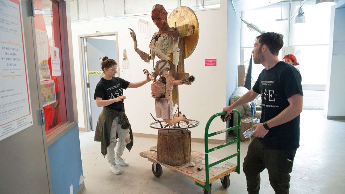 Michel Amabile, right, and Julia McGehean move one of Amabile's sculptures from his studio to the gallery.