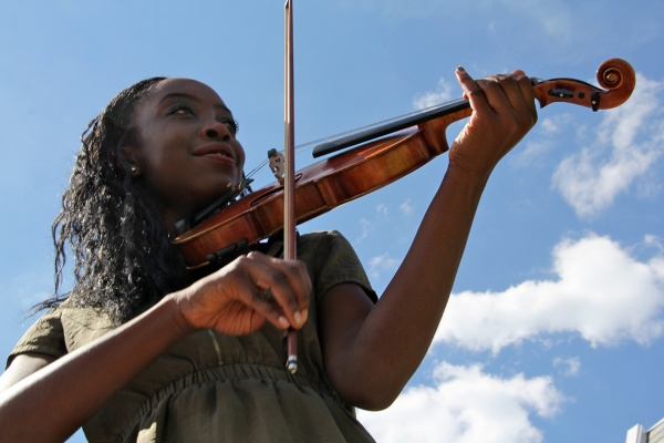 Gomian Konneh, 17, plays her violin in her East Oak Lane neighborhood. She is a senior at Masterman High School where extracurricular activities are on the chopping block.