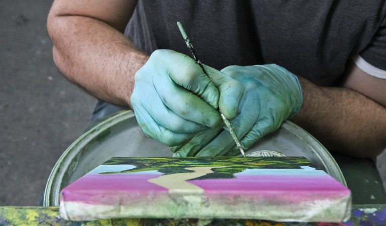 Fabian Lopez works on an abstract landscape painting in his Philadelphia studio.  (Kimberly Paynter/WHYY)