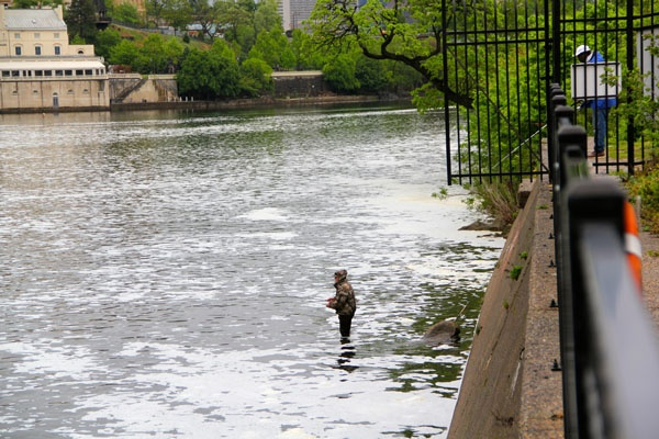 Fishermen try their luck in the Schuylkill near the Fairmount Dam. Fishing is prohibited within 100 feet of the fish ladder. (Emma Lee/for NewsWorks)