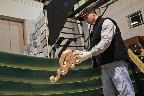 <p>Ryan Eells, mummer for 15 years, of the Jokers Brigade spray paints a prop for the 2013 show. (Kimberly Paynter/WHYY)</p>