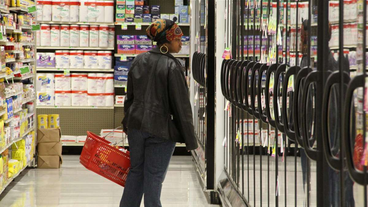 A customer browses the refrigerated cases at Fare and Square. (Emma Lee/WHYY)