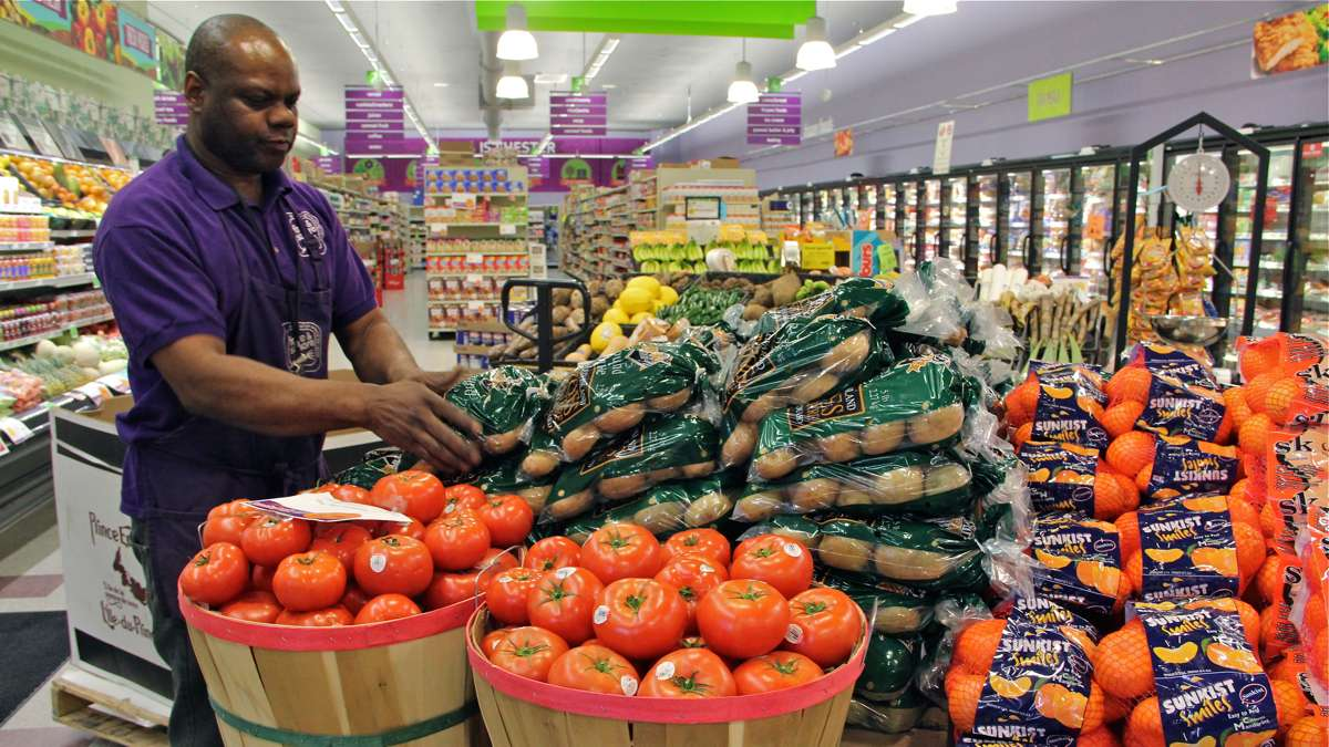 Produce manager Nate Sumpter arranges fresh fruits and vegetables at Fare and Square in Chester. (Emma Lee/WHYY)