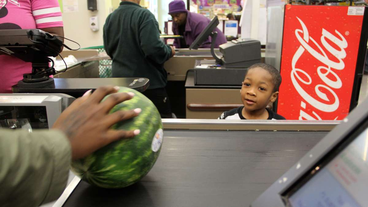 Tyrone Thomas, 5, shopping with his mother, Atoshia White, watches eagerly as his watermelon slides by the register. (Emma Lee/WHYY)