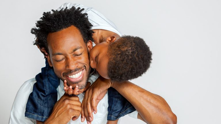 (<a href='https://www.bigstockphoto.com/image-147630257/stock-photo-an-african-american-boy-on-the-shoulders-of-his-father-leans-over-to-kiss-him-on-the-cheek-his-father-laughs-with-closed-eyes'>ITLPhoto</a>/Big Stock Photo)
