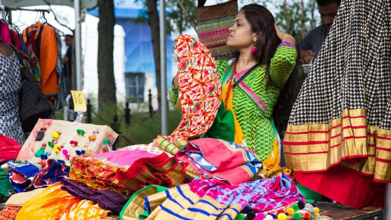 Nirali Dhada sorts her saris for sale during the Festival of India at Penn's Landing. (Emily Cohen for NewsWorks)