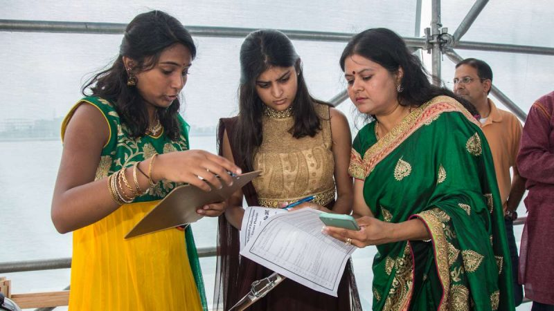 Manisha Jain, the cultural chairperson for the Festival of India (right), goes over the order of dance groups with emcees Priya Ganesh (far left) and Anika Sangal. (Emily Cohen for NewsWorks)