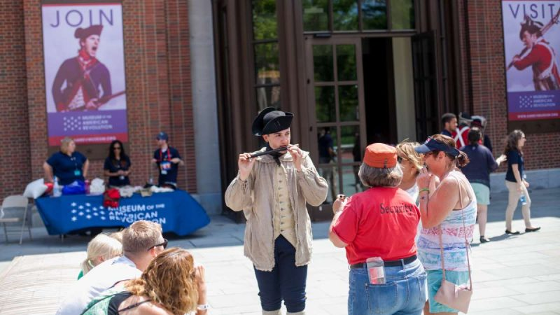 Matthew Skic, assistant curator of the event, demonstrates the fife to museum goers out outside of the Museum of the American Revolution Saturday. (Brad Larrison for NewsWorks)
