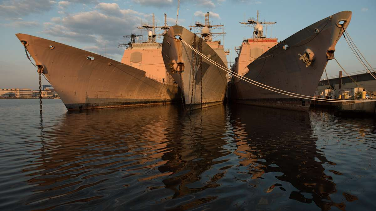 Three ships are reflected in the water at the Philadelphia Navy Yard.