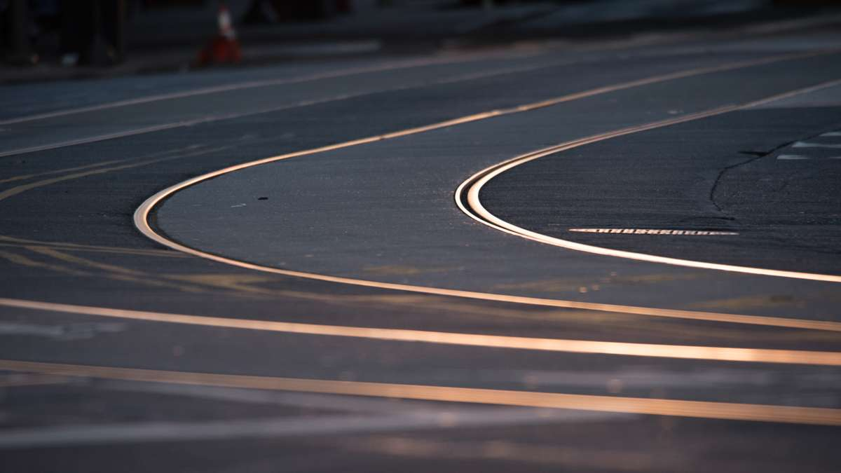 Curving trolley tracks on Girard Avenue shine pinkish-silver against the gray of the street in the pre-dawn light.