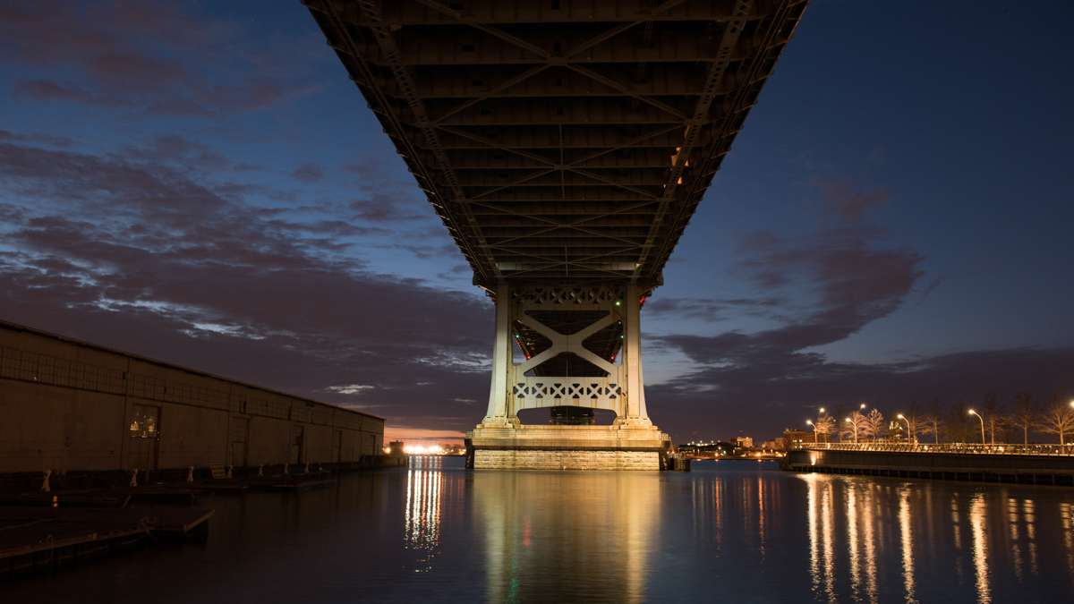 The underside of the Ben Franklin Bridge is silhouetted against the pre-dawn sky while the river reflects the still glowing street lights.