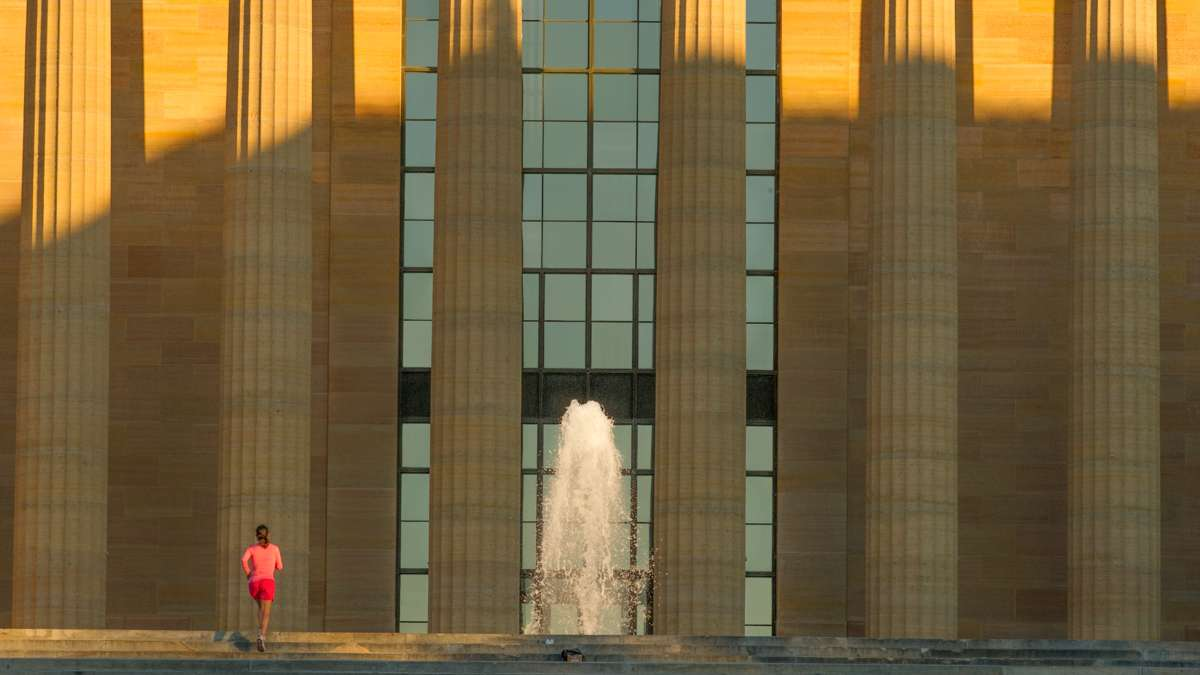 A woman in red shorts and pink shirt runs up the steps of the Philadelphia Art Museum toward the fountain while the rising sun casts long shadows.