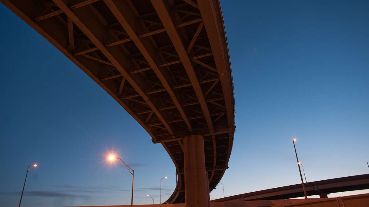The sky glows blue with pre-dawn light as seen from beneath a highway overpass.