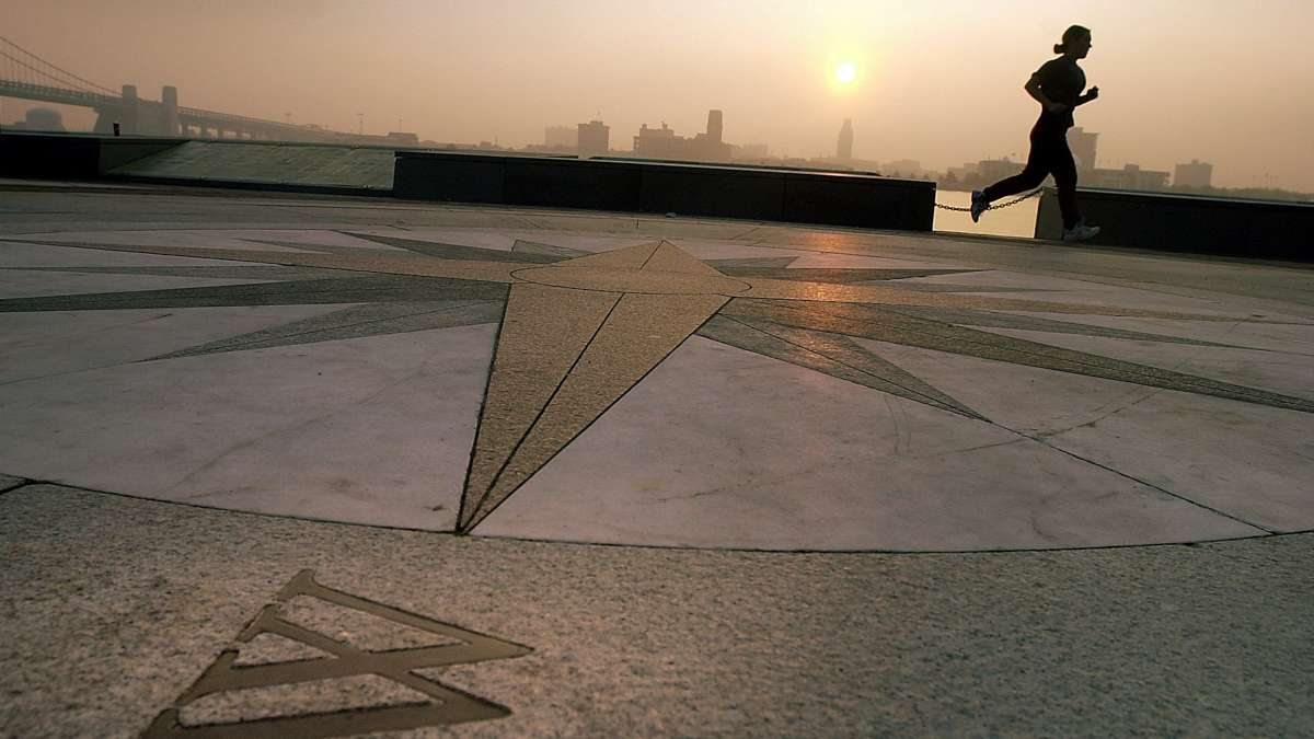 A woman jogs past a compass embeded in the floor of the amphitheater at Penns Landing as the sun rises over the Delaware River.