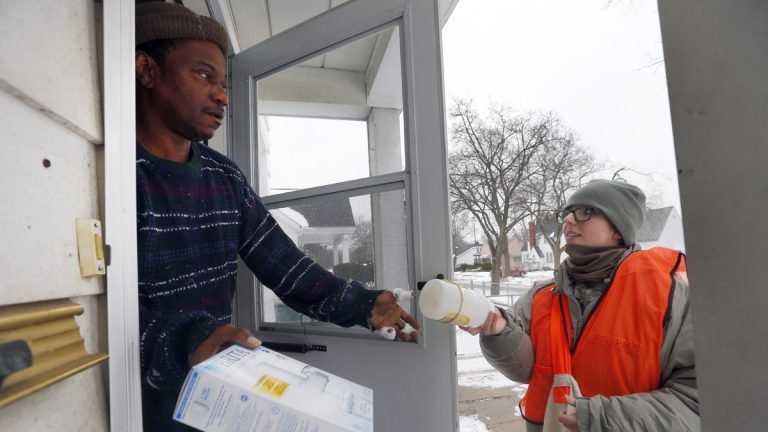 Louis Singleton receives water filters and a test kit from Michigan National Guard Specialist Jelena Tasevska Thursday, Jan. 21, 2016 in Flint, Mich. The National Guard, state employees, local authorities and volunteers have been distributing lead tests, filters and bottled water during the city's water crisis. (AP Photo/Paul Sancya)