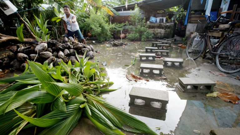 David Losia, 21, cuts coconuts for the family pigs in front of his family house flooded by the rising tides where cinder blocks are used as a makeshift walkway in Funafuti, Tuvalu. (AP Photo/Richard Vogel)