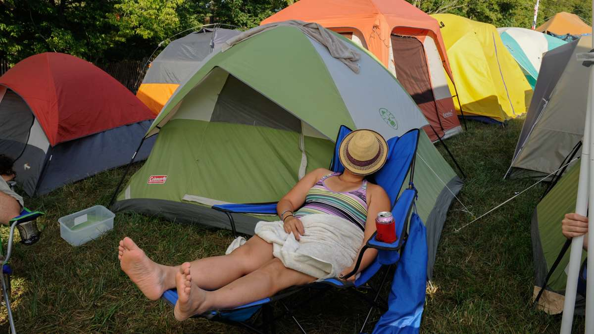 A camper catches up on her sleep in the shade of a tent in the campgrounds.