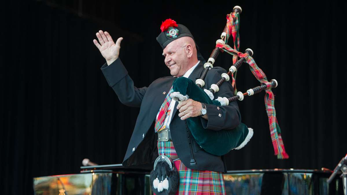 Bagpiper Dennis Hangey acknowledges the audience at the opening of the Saturday night concert. Hangey has been opening Folk Festival concerts for more than 35 years.