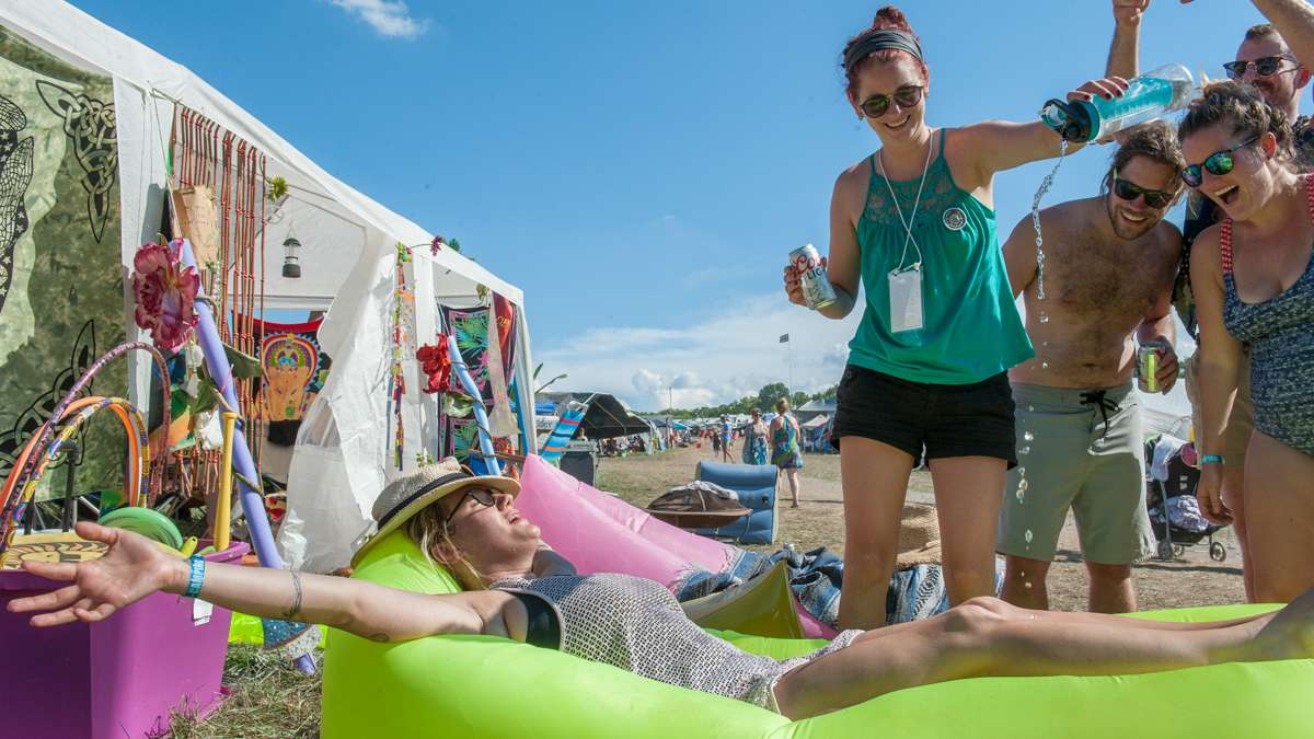 Brooke Murray stretches out on an inflatable cushion in the campgrounds while Kathleen Shaw pours water on her.