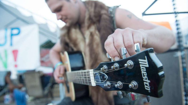 Evan Abrams of Runnemede, New Jersey, tunes his guitar in the campgrounds at the Philadelphia Folk Festival in Schwenksville, Pennsylvania. (Jonathan Wilson for NewsWorks)