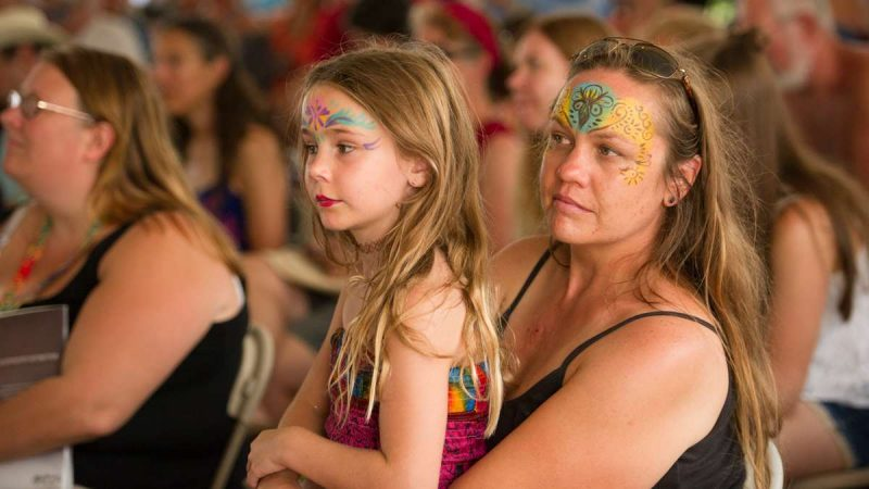 Cindy Irvin and her daughter Vera Meredith listen to Susan Werner perform in the Culture Tent. Irvin has attended 20 festivals while her daughter has attended four. (Jonathan Wilson for NewsWorks)
