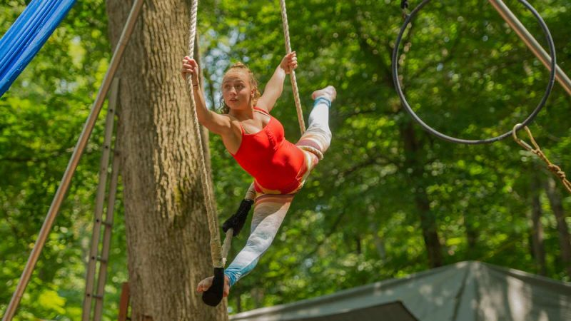 Cassie Haberle, 13, performs on the trapeze in Dulcimer Grove. Haberle is a performer with the Give and Take Little Circus. (Jonathan Wilson for NewsWorks)