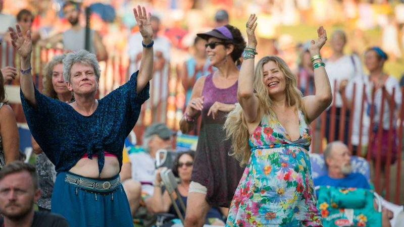 Audience members rise to their feet and begin dancing during the Baile An Salsa performance at the Philadelphia Folk Festival at the Old Pool Farm in Schwenksville, Pennsylvania. (Jonathan Wilson for NewsWorks)