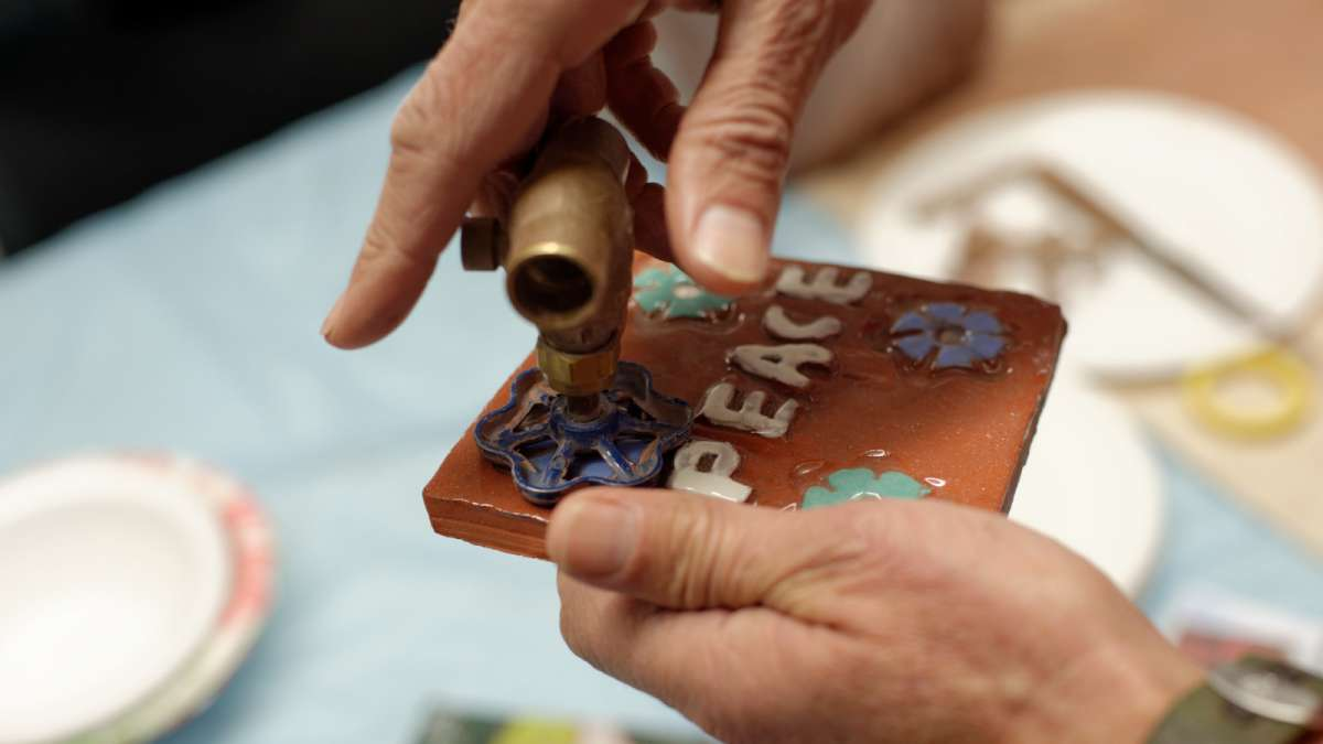 Joe Brenman demonstrates how simple tools, like this tap, are used to press motifs into clay tiles.  (Bastiaan Slabbers/for NewsWorks)