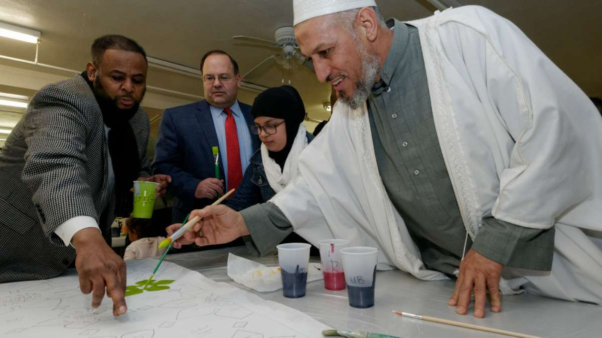 Councilman Curtis Jones Jr. points out to Al Aqsa Imam Muhammad Shehata where to apply paint. (Bastiaan Slabbers/for NewsWorks)