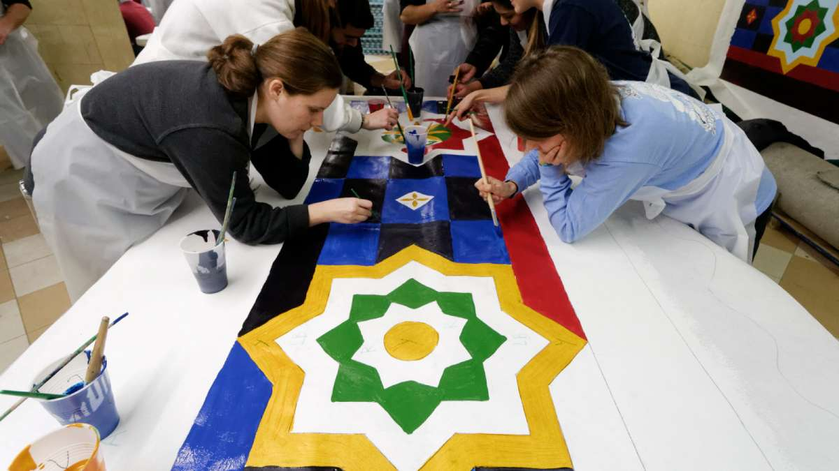 Community members help fill in the decorative elements of what will become parts of a banner along the building's roof. (Bastiaan Slabbers/for NewsWorks)